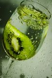 Splashes and piece of fruit in the glass of water. Glass of water with green on the grey background Stock Photo