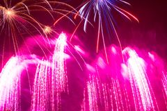 Splashes of pink bright beautiful fireworks in the night sky on. New Year`s Eve Royalty Free Stock Photography