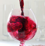 Splashes of red whine while filling a glass Stock Image