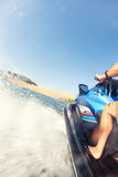 Splashes rushing out of a jet ski during a fast fun ride on a la. Ke on a sunny summer day Royalty Free Stock Images