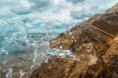 Splashes of sea water in dam on the stones royalty free stock photography