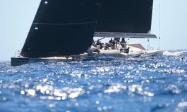Competitors during Wally class regatta in mallorca. Splashes during Wally sailing maxi class ships compete during their regatta at Palmavela sailing race in Stock Photos
