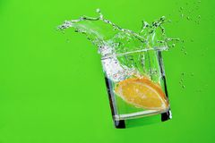 Splashes of water, lemon falling into a glass, Royalty Free Stock Images