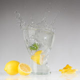 Splashes of water, lemon falling into a glass Stock Image