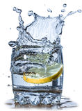 Splashes of water, lemon falling into a glass Royalty Free Stock Photos