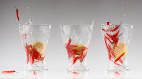 Splashes of water from the red hot pepper and lemon in a glass. Collage. Acute freshness concept Stock Photos