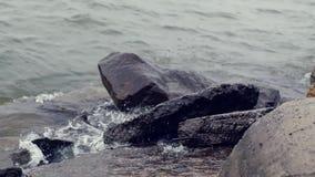 Splashes of waves break against large stones. HD, 1920x1080, slow motion. Splashes of waves break against large stones stock footage