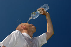 Splashing. Young man with a bottle of water Royalty Free Stock Photography