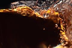 Splashing of alcoholic drink on a black background Stock Images