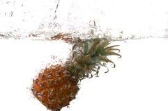 Splashing ananas. Series of splashing fruits. Splashing ananas on white. Series of splashing fruits stock photo