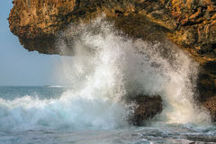 A splashing big wave crashing into the rocks Stock Images