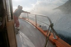 Splashing the boat. And two crew members by the big wave Stock Photos