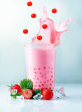 Splashing boba tea with falling pearls royalty free stock photography