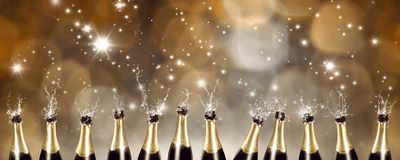 Splashing Champagne bottles with blurred lights in the background. A row of splashing champagne bottles with blurred lights in the background stock images
