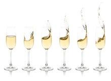 Splashing Champagne Flutes. Six champagne flutes with splashing champagne royalty free stock photos