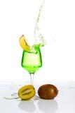 Splashing champagne. Stemmed champagne glass with kiwi liquor splashing out, isolated on white background royalty free stock photos