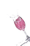 Splashing champagne. Stemmed champagne glass with liquor splashing out, isolated on white background stock photos