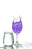Splashing champagne. Stemmed champagne glass with liquor splashing out, isolated on white background royalty free stock image
