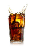 Splashing cola in glass Stock Images