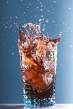 Splashing drink in glass Stock Images
