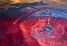 Splashing drop of water. Details of splashing drop in colorful water Royalty Free Stock Image
