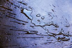 Splashing and dropping to the floor. Spilling water, splashing and dropping to the floor. purple dark background for design and text. abstract photo with stock photos
