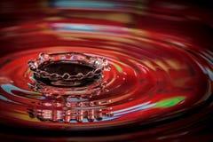 Splashing drops of red water. Macro view of splashing drops of red water causing a ripple Royalty Free Stock Photo