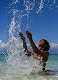 Splashing exotic boy. Exotic tanned boy splashing water all over his head in the sky on a tropical beach Royalty Free Stock Image