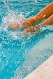 Splashing Feet. Sexy tanned womans legs and feet splashing in a blue swimming pool Stock Photo