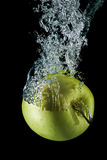 Splashing golden apple. Royalty Free Stock Photography