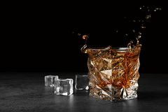 Splashing golden whiskey in glass with ice cubes on table royalty free stock photo