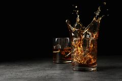 Splashing golden whiskey in glass with ice cubes on table. stock images