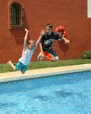 Splashing good time. Two boys jumping into a swimming pool Stock Images