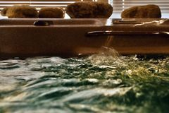 Splashing green water level in whirlpool with stones Royalty Free Stock Images