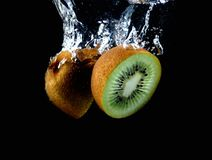 Splashing kiwi fruit on the water Stock Photography