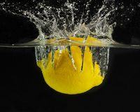 Splashing lemon into a water stock image