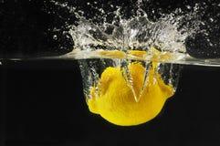 Splashing lemon into a water stock photos