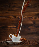 Splashing liquid of coffee and milk into white cup on wooden table Royalty Free Stock Photo