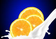 Splashing milk with orange Stock Images