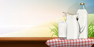 Splashing milk in transparent glass with bottle, lot of drops and full jug of milk standing or red checkered napkin Royalty Free Stock Image