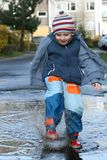 Splashing in a mud puddle. Little boy splashing in a mud puddle Royalty Free Stock Photos