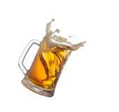 Splashing mug with beer isiolated on white . Royalty Free Stock Photography