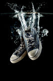 Splashing old dirty sneakers on a black stock photos