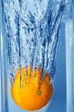 Splashing orange into a water Royalty Free Stock Images
