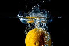 Splashing orange on water Royalty Free Stock Photography