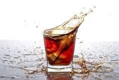 Splashing out of the glass from falling ice cubes Royalty Free Stock Photos