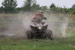 Break through. Offroad quad racer getting wet by a big splash stock image
