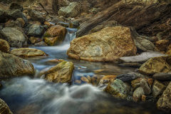 Splashing Through the Rocks. Slow motion river in the Wasatch mountains of Utah USA with a bit of snow left Stock Photography