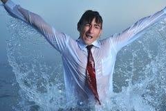 Splashing in sea. Young businessman splashing in water, close up Royalty Free Stock Image