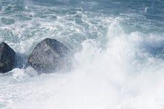 Splashing sea over rocks. Dramatic image of the Splashing sea water hitting over large rocks Royalty Free Stock Images